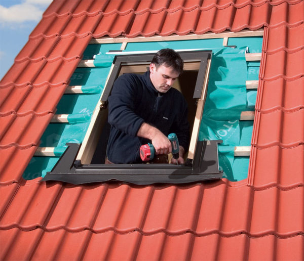 Рабочий устанавливает раму окна