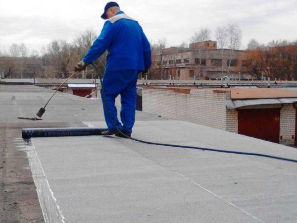 Рабочие ремонтируют крышу гаража