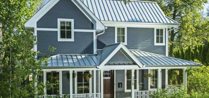 Фальцевая крыша с матовым покрытием серого цвета красиво гармонирует с деревянной архитектурой загородного дома в стиле кантри.